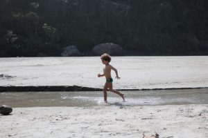 Cauê correndo no rio na praia de Itamambuca, Ubatuba